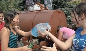 Мокрый флешмоб на площади Победы: юные горловчане простились с летом, обливая друг друга водой